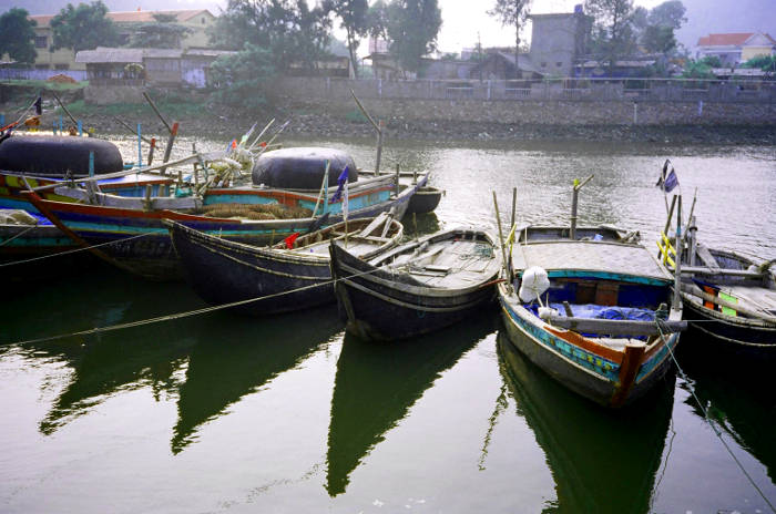 Two (and a piece of a 3rd) of the Persian Slipper style of diesel powered, basket built fishing boats, photographed in Cua Lo in 2006.