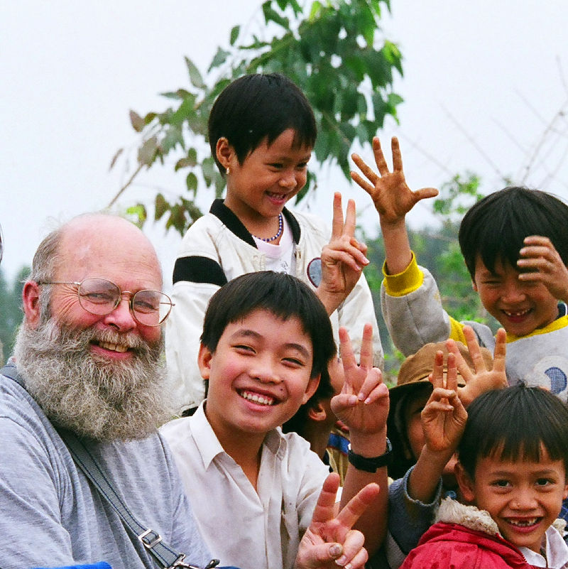 Ken poses with a group of Vietnamese kids
