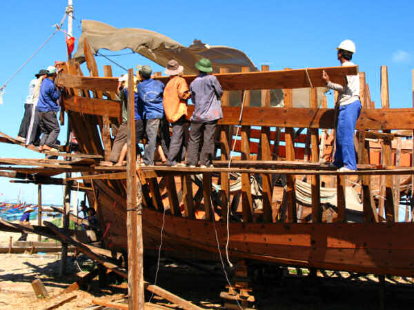 Modern Motor Fishing Vessel under construction: a crew of workmen put a long, 2 inch thick plank into place.