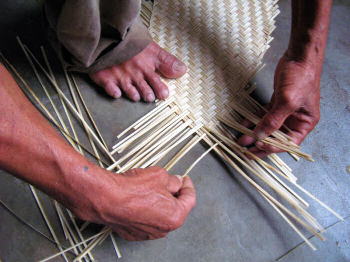 The bamboo hull of a model woven bamboo boat, being woven flat against the floor.